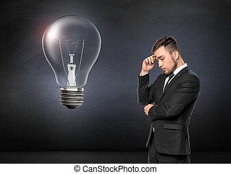 jeune homme, dans, costume, pensée, sur, mur concret, arrière-plan., cassé, lumière, bulb., concept affaires