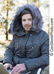 jeune homme, dans, fourrure, capuchon, veste, portable utilisation, dans, les, forêt