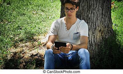 jeune homme, dans, parc ville, utilisation, ebook, lecteur
