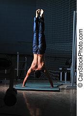 jeune homme, exécuter, handstand, dans, fitness, studio