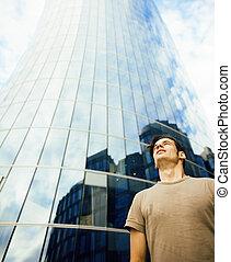jeune homme, stand, devant, affaires modernes, bâtiment