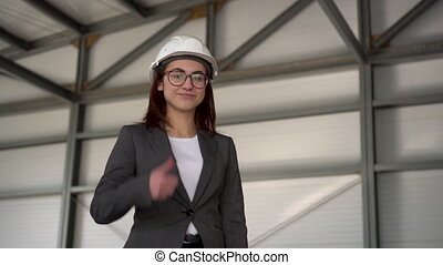 jeune, site., femme, appareil-photo., construction, patron, spectacles, casque, regarde, complet, pouce, protecteur