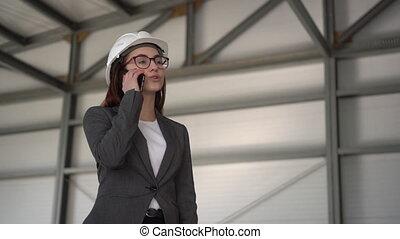 jeune, site., femme, parle, conversation, téléphone., construction, patron, casque, téléphone, complet