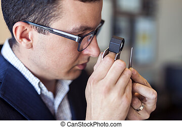 Jeweler examining diamond through loupe - Jeweler examining...