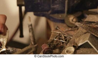 Jeweler in workshop creating brass pendant - Shot of Jeweler...