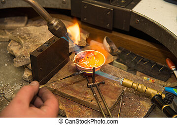Jeweler melting gold in crucible with gasoline burner