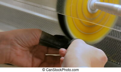 Jeweler polishes gold jewelry - Hands of jeweler polishes...
