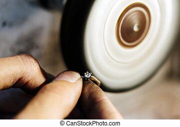 Jeweler polishing jewelry with tools