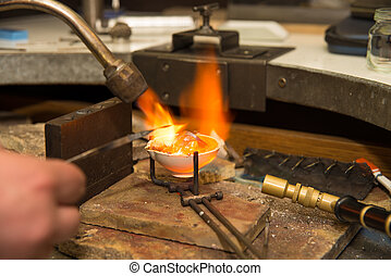 Jeweler melting gold in crucible with gasoline burner