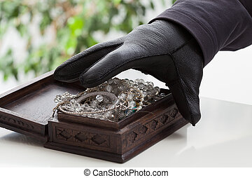 Jewelery box - A closeup of a hand of a man about to steal a...