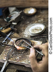 Vertical close up shot of Jeweler crafting golden rings with flame torch.