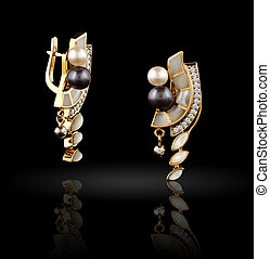 Pair of gold earrings on black background