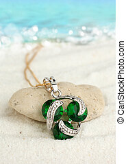 Jewellery pendant on sand beach with sea background, soft focus