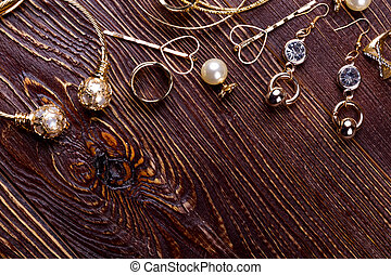 Jewelry on wooden background. Golden rings and earrings....