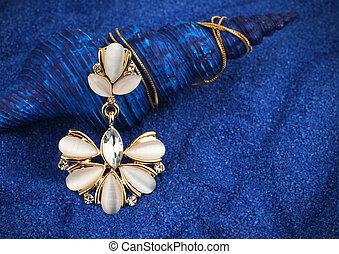 Jewelry pendant with nacre and diamonds on dark blue seashell background
