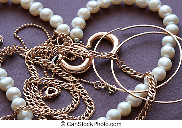 Jewelry - Closeup of various gold and pearl jewelry on brown...
