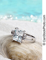 Jewelry ring with clean diamond on sand beach background, soft focus