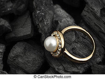 jewelry ring with diamond and pearl on black coal background, copy space