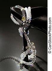 jewel necklace around a fashion black shoe heel on dark background