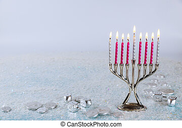 Jewish candlestick menorah with burning candles on sparkle background.