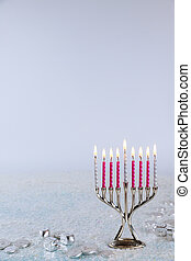 Jewish candlestick menorah with burning candles on white background.