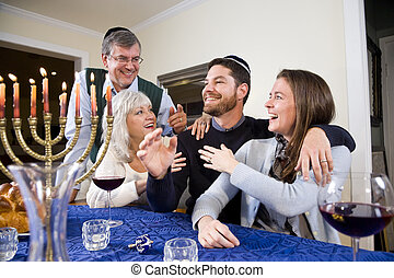 Jewish family celebrating Chanukah at table with menorah