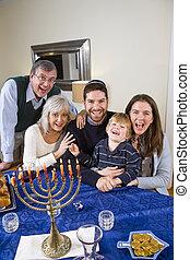 Jewish family celebrating Chanukah at table with menorah