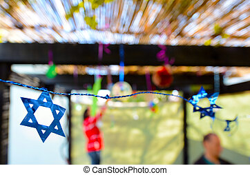 Jewish family decorating Sukkah for the Jewish festival of...