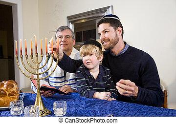 Jewish family lighting Chanukah menorah - Three generation...