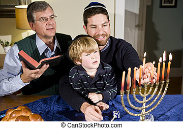Four year old boy with grandfather and father lighting Hanukkah menorah