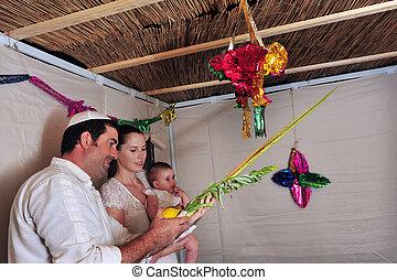 Jewish Festival of Sukkot - Israeli family bless on the four...