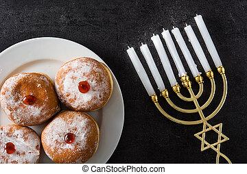Jewish Hanukkah menorah and sufganiyot donuts on black background