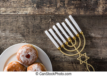 Jewish Hanukkah menorah and sufganiyot donuts on wooden table