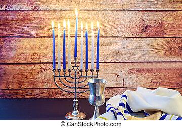 Jewish Holiday Hanukkah background with menorah wood dreidel...