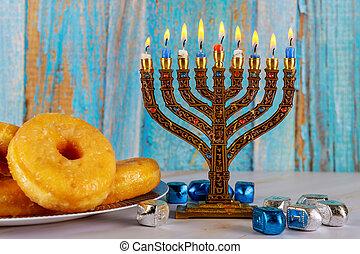 Jewish holiday Hanukkah with menorah, donuts and dreidels.