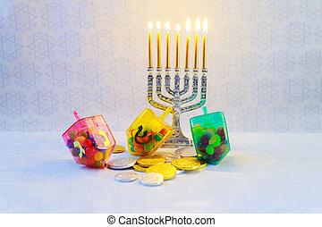 jewish holiday Hanukkah with menorah, wooden dreidels