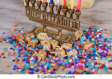 Image of jewish holiday Hanukkah with wooden dreidel spinning top on the glitter background
