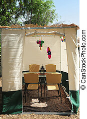 Jewish Holiday Sukkoth - A sukkah with table, chairs and...