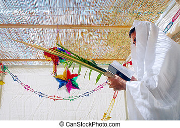 Jewish Holidays - Sukkot - A Jewish man blesses on the four...