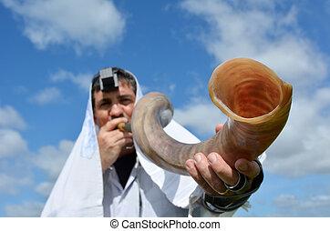 Jewish man blow Shofar outdoors under the sky, on the Jewish...