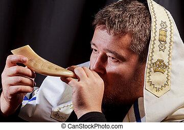 Jewish man blowing the Shofar horn of Rosh Hashanah New Year...
