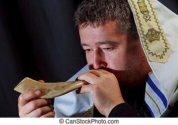 Jewish man in Tallit blowing the Shofar horn of Rosh Hashanah New Year