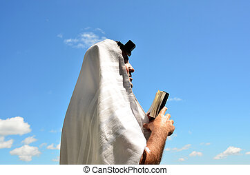 A Jewish man wearing Tallit and Tefillin read from the Torah book pray to God under a blue sky with sheep clouds.