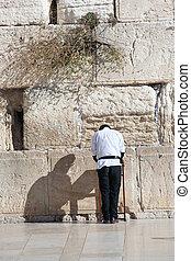 Jewish man praying at tearing wall