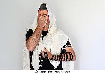 Jewish man praying with Tallit and Tefillin