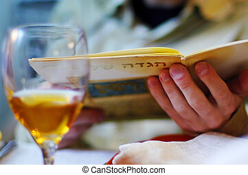 Jewish man reads the Haggadah on Passover Seder Meal