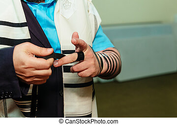 Jewish Man wrapped in tefillin pray . A religious orthodox...