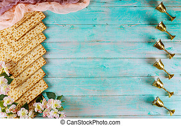 Jewish matzah bread on blue background with six wine cups and flowers. Passover holiday concept