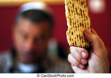 Jewish men is blessing on Matzah (unleavened bread) while...