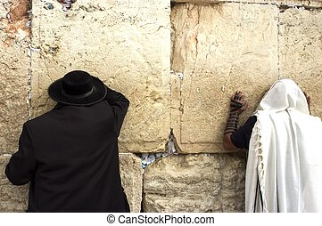 Jewish orthodox men pray at the western wall in the old city of Jerusalem, Israel